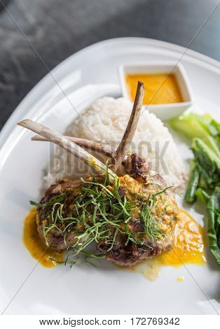 Grilled Lamb steak with spicy yellow sause and green vegetable on jasmine rice.