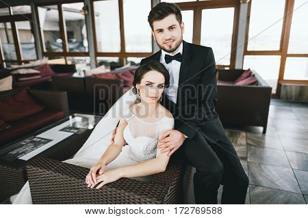 Attractive bride and bridegroom sitting at big window at background, looking at camera and smiling, wedding photo.