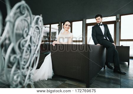 Beautiful bride and bridegroom sitting at big window at background and smiling, wedding photo.