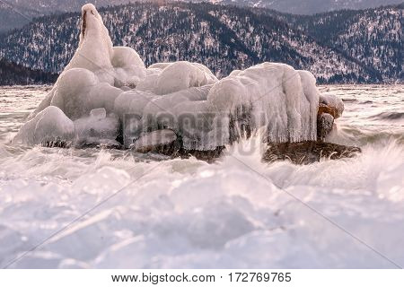 Beautiful winter view with an iceberg in the waters of the lake and ice on the bank on the background of mountains at dawn