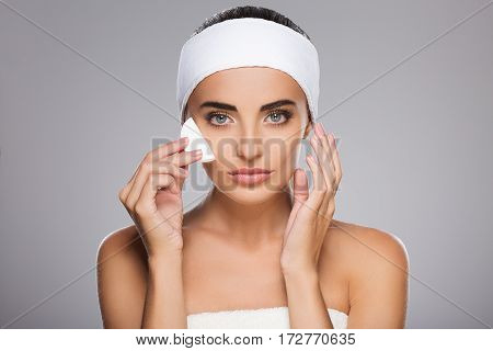 Nice girl with brown hair fixed behind, clean fresh skin, big eyes and naked shoulders wearing white bandage, posing at gray studio background with cleaning sponge near face.