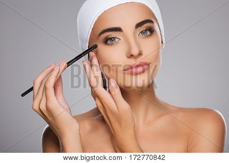 Gorgeous girl with brown hair fixed behind, clean fresh skin, big eyes and naked shoulders wearing white bandage, doing make up at gray studio background.