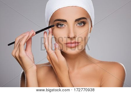 Cute girl with brown hair fixed behind, clean fresh skin, big eyes and naked shoulders wearing white bandage, doing make up at gray studio background, portrait.