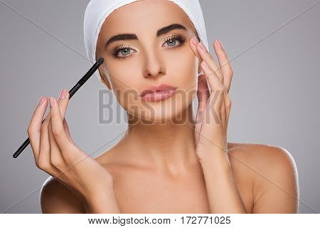 Beautiful girl with brown hair fixed behind, clean fresh skin, big eyes and naked shoulders wearing white bandage, doing make up at gray studio background.