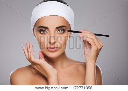Perfect girl with brown hair fixed behind, clean fresh skin, big eyes and naked shoulders wearing white bandage, doing make up at gray studio background, portrait.