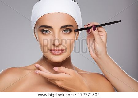 Lovely girl with brown hair fixed behind, clean fresh skin, big eyes and naked shoulders wearing white bandage, doing make up at gray studio background.