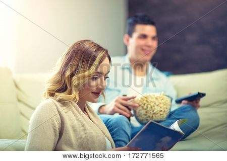 Woman reading magazine. Happy young man sitting on the sofa at home with popcorn and beer watching TV. Focus on woman.