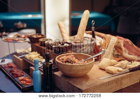 Buffet salad olive bread and jamon. Breakfast buffet with salad and olive bread jamon on a thick wooden board with a knife and souce. Soft focus.
