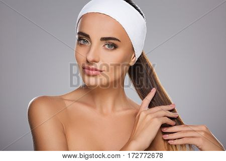 Pretty girl with brown hair fixed behind, clean fresh skin, big eyes and naked shoulders wearing white bandage, posing at gray studio background, a model with light nude make-up.
