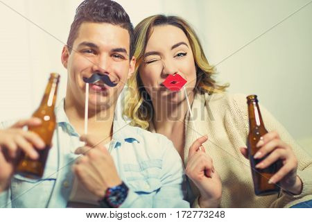Young couple having fun holding artificial mustache and lips stick and beer
