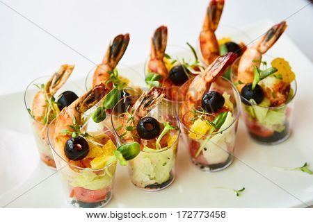 Shrimp, avocado, tomato, salmon cocktail salad served in a glass