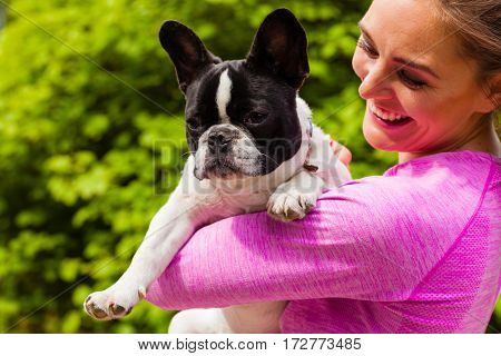 Animal lover little pets dogs fun concept. Happy smiling woman wearing sport clothes holding small cute French Bulldog in park outside