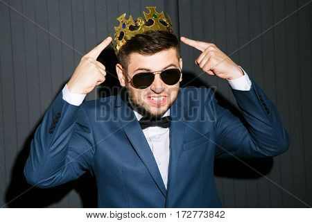 Man in sunglasses wearing suit with bow and crown on head. Pointing at crown on head. Cool, fancy look. Waist up, studio, indoors