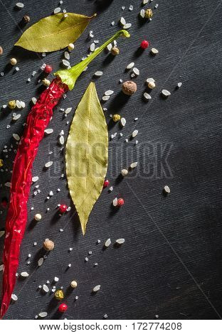 Red Pepper Pungent Spices And Bay Leaf On The Black Tree. View From Above.