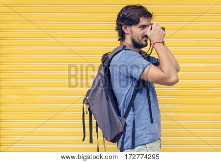 Man taking a photo yellow wall background