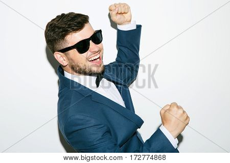 Man in sunglasses wearing suit with bow. Feels good, dancing, smiling, hands raised, fists clenched. Waist up, studio, indoors