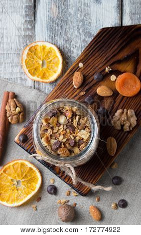 Homemade granola with nuts and dried oranges in jar with copy space on wooden background, top view