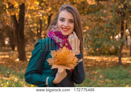 girl stands on the street smiles and keeps the leaves