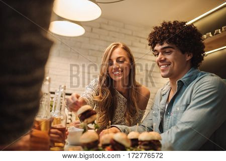 Couple enjoying a fast food at home.