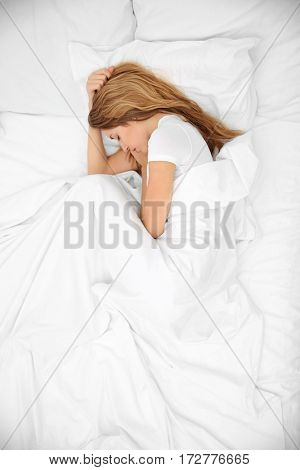 Young attractive woman sleeping in bed, top view