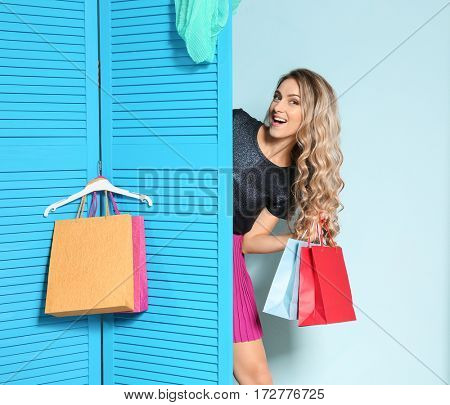 Woman with shopping bags looking out blue folding screen