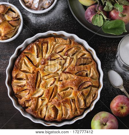 Homemade big and small apple cake pie in white ceramic forms with fresh apples with leaves, sugar powder, and tin can of sugar over dark wooden background. Top view