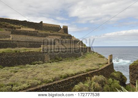 Agricultural terracing built with lava-stone with sea and blue sky in background picture from Puerto de la Cruz Tenerife Spain.