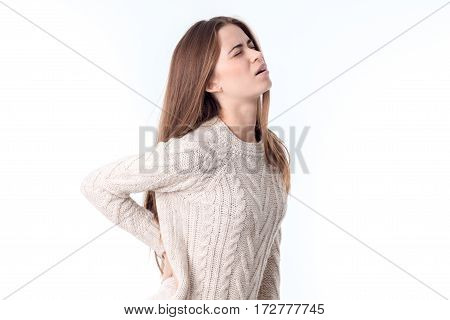 the girl stands sideways and chvvstvuet back pain is isolated on a white
