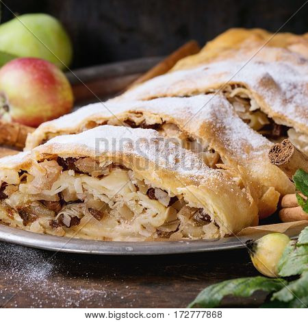 Sliced homemade apple strudel served with fresh apples with leaves, cinnamon sticks and sugar powder on vintage metal tray over old wooden background. Close up, dark rustic style