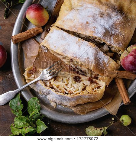 Sliced homemade apple strudel served with fresh apples with leaves, cinnamon sticks and sugar powder on vintage metal tray with fork over old wooden background. Overhead view, rustic style