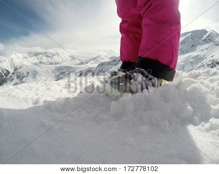 Girl's skiing boots on snow-body part