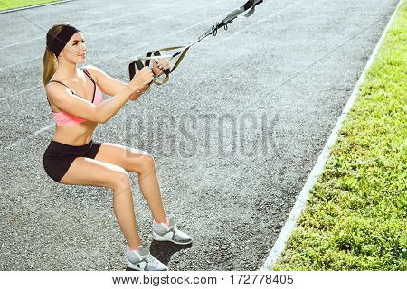 Sport, exercises with training loop outdoors. Profile of girl in rose top and black shorts doing exercises with training loop on stadium. Sporty woman in good shape squatting with training loop, full body, closeup