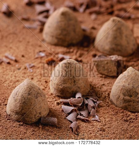 Chocolate truffles with black chocolate flakes and cocoa powder as background. Close up