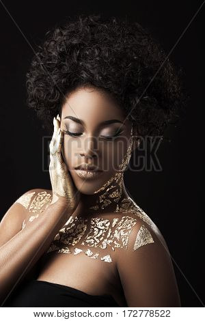 Afro-American girl with curly hair in black dress. Make-up, hairdo. Covered with golden patterns. Closed eyes, hand on cheek. Waist up, indoors, studio