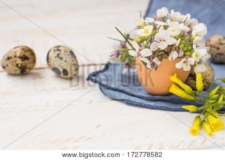Bouquet of white yellow flowers in eggshell quail eggs blue napkin on wood table Easter interior decoration close up