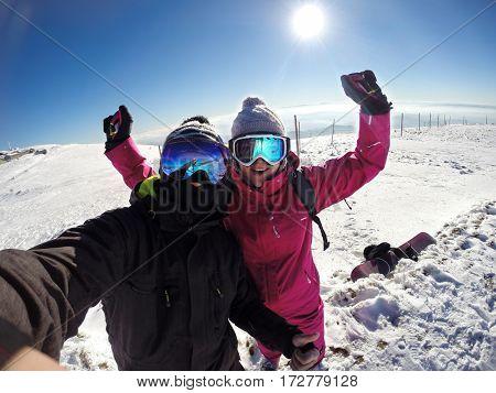 Nice cheerful couple on skiing in mountain