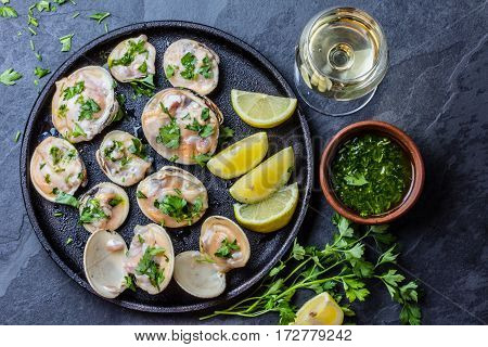 Fresh raw clams with lemon, herbs and white wine on blackiron plate on stone slate background. Top view