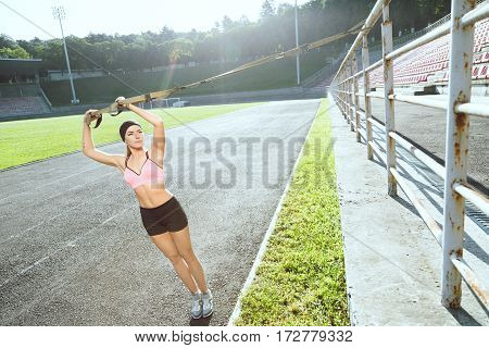 Sport, exercises with training loop outdoors. Girl in rose top and black shorts doing exercises with training loop on stadium. Sporty girl in good shape looking aside, side view, full body