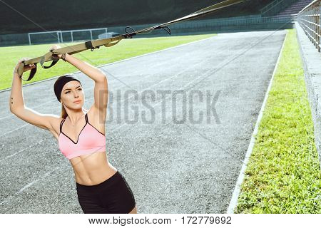 Sport, exercises with training loop outdoors. Girl in rose top and black shorts doing exercises with training loop on stadium. Sporty girl in good shape looking aside, side view