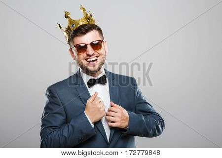 Stylish young man in suit with bow and sunglasses. Wearing crown. Looking at camera and laughing. Outrageous, fancy look, cool. Waist up, studio, indoors