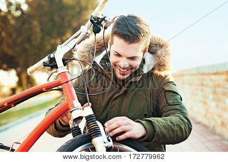 Young Man Checking Brake On Bike