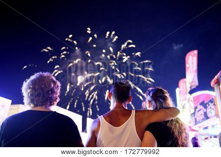 Unrecognizable people admiring the fireworks against blue night sky at luna park