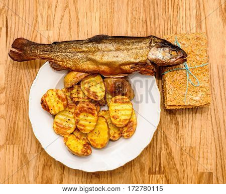 Delicious crispbread tied with organic blue thread on wooden oak table next to smoked fish and baked patatoes