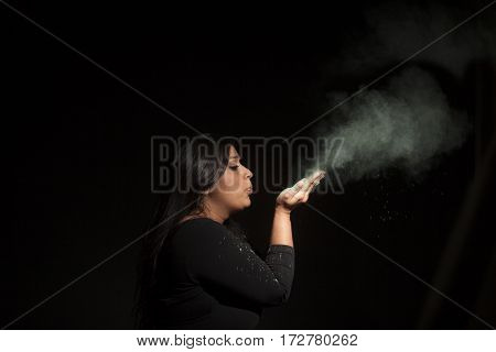 indian woman blowing green dust isolated on black background