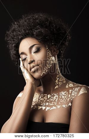 Beautiful Afro-American girl with curly hair in black dress. Make-up, hairdo. Covered with golden patterns. Closed eyes, hand on cheek. Waist up, indoors, studio