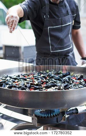 Chef man is preparing mussels on a large frying pan on the street adding salt