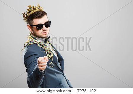 Stylish young man in suit with bow and sunglasses. Wearing crown, confetti on shoulders. Pointing at camera. Outrageous, fancy look, cool. Waist up, studio, indoors