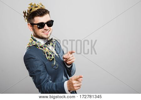Stylish young man in suit with bow and sunglasses. Wearing crown, confetti on shoulders. Pointing at camera and smiling. Outrageous, fancy look, cool. Waist up, studio, indoors