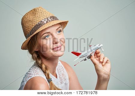 Closeup portrait of beautiful woman in straw hat holding airplane model in hand, dreaming about holidays
