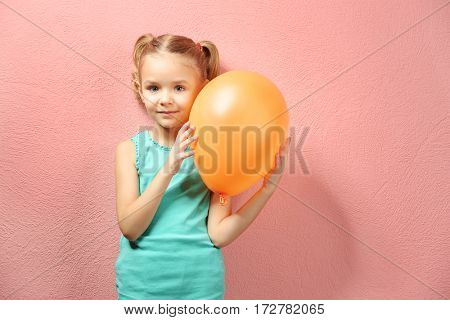 Cute little girl with balloon on pink background